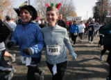 Theresa McGuire , left, and Jill Peterson get in the spirit of things as they run in the Mile High...