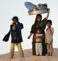 BAG103 - Iraqi children look on from a hill as a girl carries pots, at a farmers settlement near...