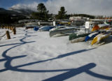 New snow covers the ground at the Frisco Marina, while rowing shells sit on dry-dock, Wednesday...