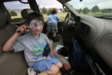 Erik Mander, 5, looks through his magnifying glass in the family car as his brother Ryan looks out...