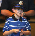 Cancer patient Travis Mickelsen (cq), age 8, holds his badge after being  sworn in as an honorary...