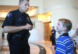 R ro L: Cancer patient Travis Mickelsen (cq), age 8, looks up at Aurora Police Officer James...