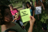 "Members of the group ""Mi Casa"" a resource center for women hold up flyers in opposition..."