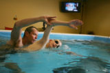 SwimLabs swim instructor and co-owner Giff Cutler (Cq) instructs Kyle Savickas, 9,  in a small...