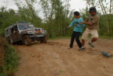 Bhupal Rajkhatiwada (right) and Dev Kumar lend some muscle to trying to free a vehicle from a mud...