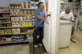 R&R Market employee Lerdy Vigil (cq), who has worked for the store for 22 years, talks with...