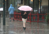 A pedestrian walks down Curtis St. in the rain,Tuesday afternoon, June 12, 2007 in Denver. After...