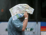 A pedestrian covers himself from the rain with a map, as he walks down the 16th Street Mall,...