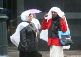 Two woman cover themselves from the rain, while waiting for a bus on 17th Street ( went back to...