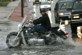 A motorcyclist doesn't let the rain wreck his ride as he goes through  several inches of standing...