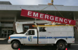 Daniel Camp , from Century Signs, takes down the emergency sign over the ER entrance after...