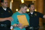 Justin Box (cq) is escorted out of Denver District court Thursday June 14,2007. Box, 17, was...