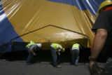 Local hired labor enter the nearly complete tent to attack the final pole positions completely...