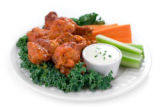 An appetizer plate of spicy buffalo wings served with dip, carrot and celery sticks. Shallow dof