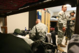 (from left) 37 year-old Major Andrew Olmsted signs a few documents as his room-mates, Master...