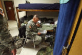 37 year-old Major Andrew Olmsted signs a few documents prior to leaving his bunk for a training...