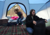 Amy Seegmiller (cq), 3, left, hops around in the tent as her mom Shareece Seegmiller (cq) unpacks...