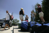 Members of a softball team from Massachusetts evacuated from Hawthorn Suites wait to be escorted...