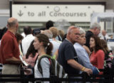 Travelers wait in line to go through security at  DIA Monday afternoon June 18, 2007. The summer...