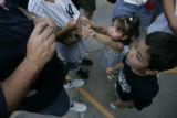 Kristen Romero, 3, and Matthew Romero (cq), 5, beg for their tickets from their father, Chris...