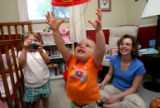 Olivia Zenzinger reaches for her favorite firefighter hat offered by dad, Ted, as Sophia, left,...
