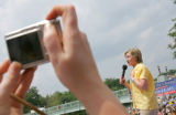 A Clinton supporter takes a photo of Hillary Clinton as she campaigns with her husband former...