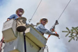 XCEL workers John Anderson (cq),left, and Norm Antonelli (cq), right, restore power to a ranch...