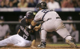 0537 Colorado Rockies Todd Helton is tagged out at home by New York Yankees catcher Jorge Posada...