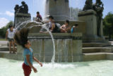 DLM0612  Water flies as Victoria Terrones, 9, flings her hair back while cooling off in the...