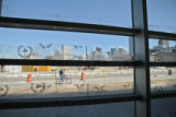 A cyclist rides down the new bike lane, seen through the windows of the nearly completed new Post...