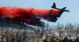 A slurry bomber drops fire retardant on the New Castle wildfire west of Glenwood Springs, Colo. on...