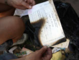 Cathy Lewis (cq) finds  her burned marriage licence while going through a bag of belongings a half...