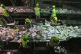 Workers sort through recyclables on a conveyer belt, Friday afternoon, June 29, 2007, at the Waste...