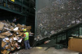 A worker sorts through cardboard, behind him is a large bin of aluminum cans, Friday afternoon,...