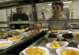 Miguel Fernandez(cq), 9, and Javon Davis(cq), 11, reach for bowls of fruit in the cafeteria at...