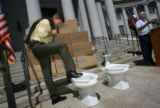 Mayor John Hickenlooper laughs at a toilet related joke by Hamlet J. (Chips) Barry III, (cq and...