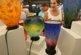 MJM363 Sue Frank (cq) of Englewood, Colo. reacts as she looks at glass vases and flowers by...