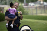 Patrol Officer Scott Marsh (cq) holds a 17-month-old kidnapping victim near 1470 S. Quebec St in...
