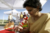 Arati Upadhyay(cq), the priest's wife, lights a candle before the start of the Pooja ceremony in...