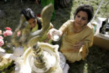 Arati Upadhyay(cq), (right), the priest's wife, and Seema Agaruwal light a candles before the...