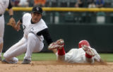Colorado Rockies infielder Kazuo Matsui, left, tags out Philadelphia's  Jimmy Rollins, right, for...