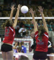 Amanda Paradisa, left, and Nicole Paradisa, right, both from Hoehne High School, go up for a block...
