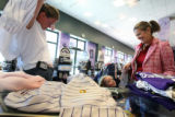 (from left) Kristin Fox (cq) tries on a Rockies shirt as her daughter, 3 year-old Elliot Fox (cq)...
