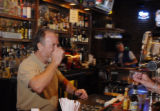 Reiver's Bar and Grille bar manager Doc Roberts (cq, left) drinks a shot of tequila with Patrick...