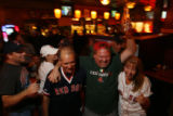 DM1267   Mike Cleary, center, celebrates with felloe Boston fans Wayne and Rena Lumbert at The...