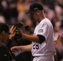 [5987]  Colorado Rockies pitcher Aaron Cook is congratulated by teammates after coming back to the...
