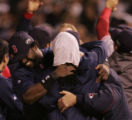 [8212]  Boston Red Sox David Ortiz, left, hugs Manny Ramirez (with towel on head) after their 4-3...