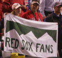 [8478]  Boston Red Sox fans hold up a sign resembling a Colorado license plate after the Red Sox...