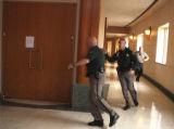 Jefferson County Sheriff Deputies (one carrying a defibulater) rush into courtroom 5A in the...