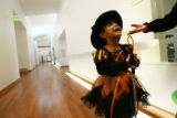 MJM875  Dressed as a witch and holding her cane, Alma Rodriguez, 5,  talks in spanish to her...